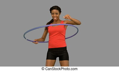 Woman playing with a hula hoop on g