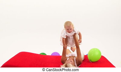 Woman playing with baby girl on floor