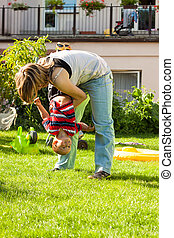 Woman playing with child outdoors