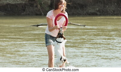 Woman playing with dog near river - Woman and her dog Jack...