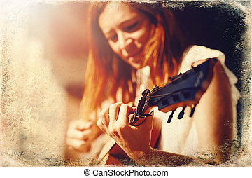 woman playing with guitar and blurred background. Old photo ...