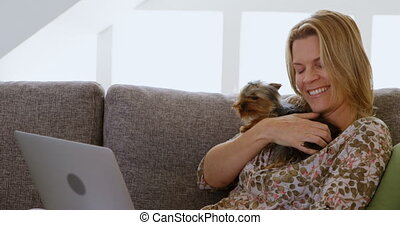 Woman playing with her dog in living room 4k
