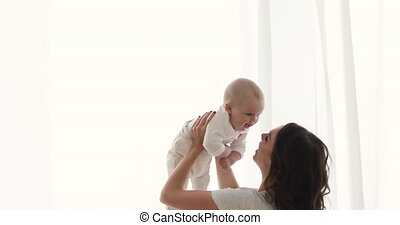 Woman playing with infant child - Cheerful woman playing...