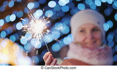 Woman playing with sparkler, her blurry face is visible in...