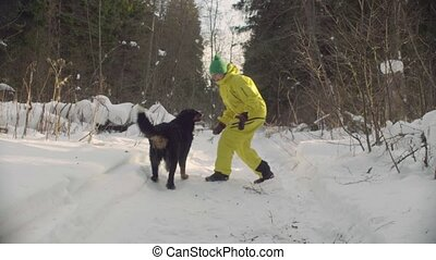 Woman playing with the dog in winter forest