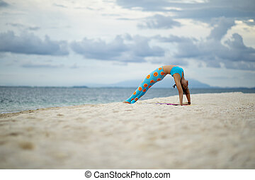 woman playing yoga pose on sand beach