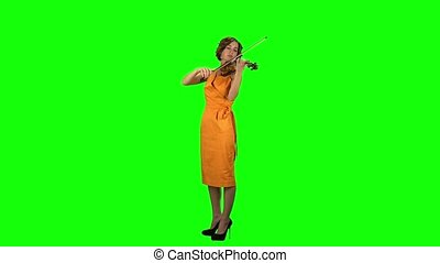 Woman plays a wooden violin. Green screen - Woman in the...