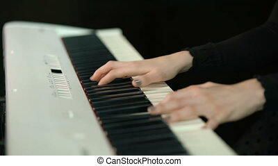 Woman plays by hands on white digital piano, close-up...