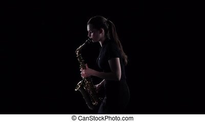 Woman plays on saxophone in slow motion. Black studio background