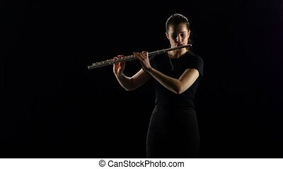 Woman plays on the flute slow melody. Black studio background