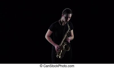 Woman plays on the saxophone blues melody in slow motion