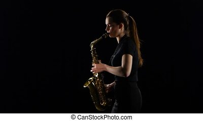 Woman plays on the saxophone slow melody. Black studio background