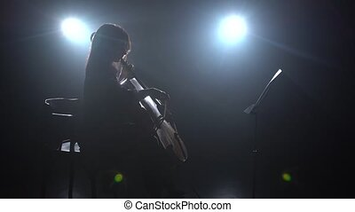 Woman plays the cello in a dark room and looks at the music stand. Silhouette. Black smoke background. Side view