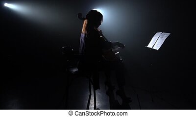 Woman plays the cello in a dark room and looks at the music...