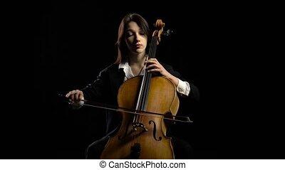 Woman plays the cello on dark studio. Black background -...