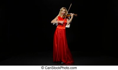 Woman plays the fiddle. Studio. Black background -...