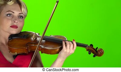 Woman plays the violin. Green screen. Close up - Woman in...