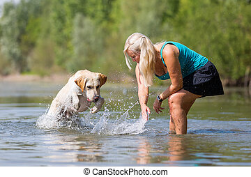 woman plays with a dog in the lake