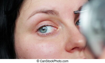 Beautiful young woman plucks eyebrows with forceps and mirror