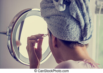 Retro instagram style image of a woman with her hair wound in a towel carefully plucking her eyebrows in the bathroom mirror.