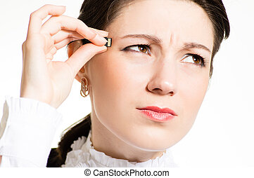 Woman plugging micro SD memory stick to her head closeup...