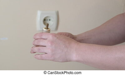 Woman plugs electric liquid mosquito repeller into the outlet close-up