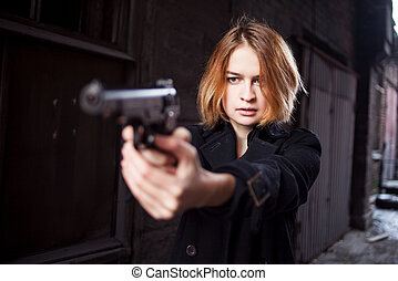 Woman pointing a gun. Mafia girl shooting at someone on the...