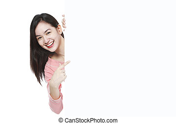 A young woman pointing at a blank white wall