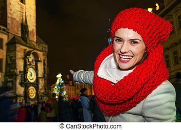 woman pointing at Christmas tree on Old Town Square in Prague