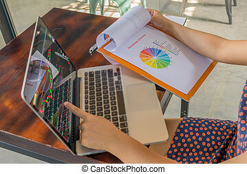 Woman pointing at financial candlestick graph on laptop at cafeteria