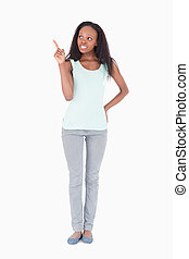 Woman pointing at something next to her on a white background
