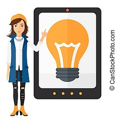 Woman pointing at tablet computer with light bulb on screen.