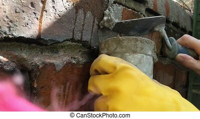 Woman pointing brick wall with mortar. Hands close up. -...