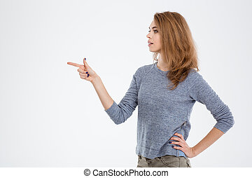 Woman pointing finger away - Portrait of a young woman ...