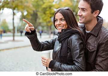 Woman pointing finger away to her boyfriend outdoors