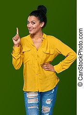 Woman pointing her finger up - Idea. Happy mixed race...
