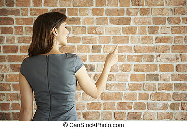 Woman pointing on the brick wall