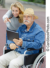 woman pointing out something of interest to disabled elderly man