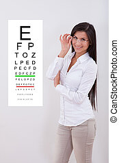 Woman pointing standing next to an eye chart