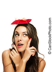 woman pointing with her fingers to the present on her head on white background