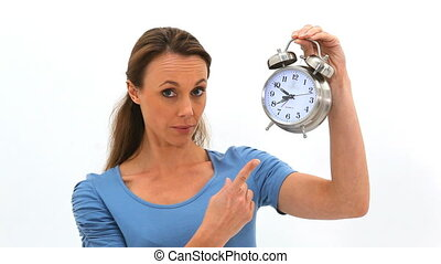 Woman points at a clock then open her mouth in surprise