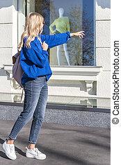 Woman points finger at shop window