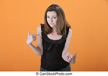 Young Caucasian woman annoyed points index finger towards herself