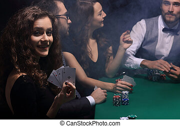 woman poker player showing a combination of four aces