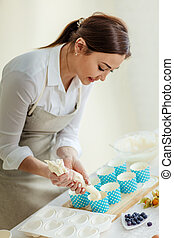 woman poring dough in the decorative cupcake liners