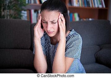 Woman portrait feeling head pain at home