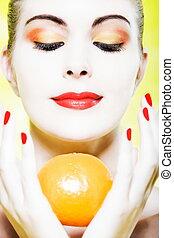 Woman portrait holding a orange smiling