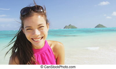 Woman portrait on beach. Multiracial model on Hawaii Lanikai beach. Young mixed race Asian Chinese / Caucasian female by ocean wearing pink sundress smiling looking at camera on summer travel holidays