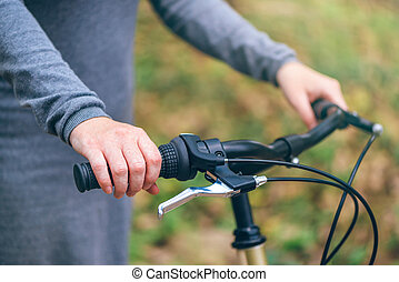 Woman poses with her bicycle in park during autumn
