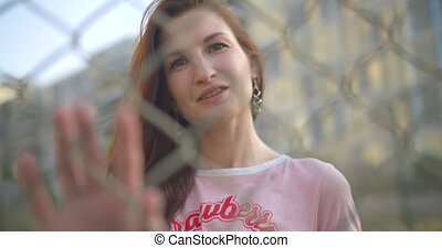 woman posing behind a netting - close-up of a cheerful girl ...